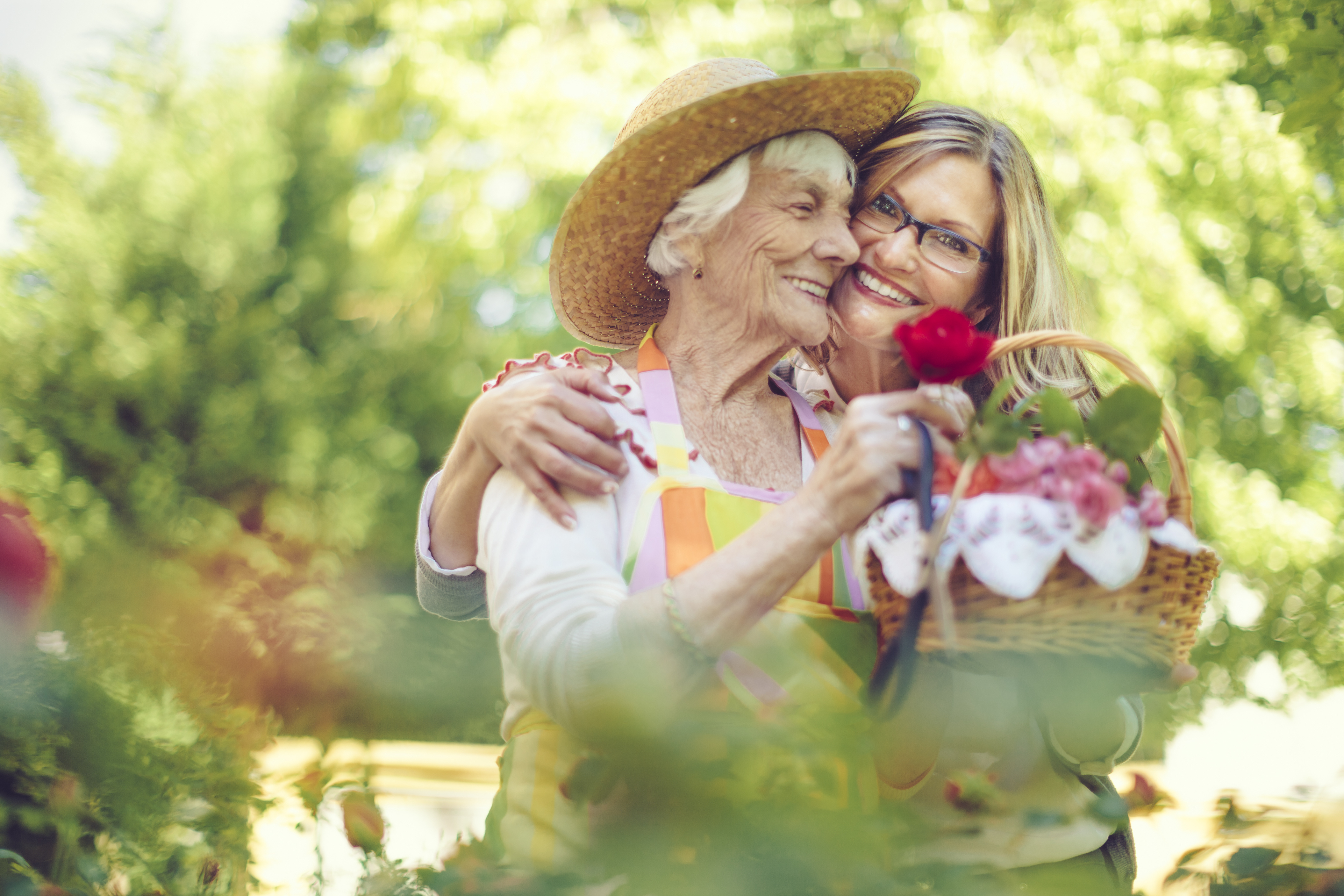 A memory care patient and a young woman hugging while holding a basket of flowers